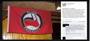 The stolen flag as a result of the physical asault on the two persons. Posted on the facebook page of the fascist group in which they praise themselves for capturing it. The picture has been subsequently deleted from the facebook page as a result of launching the international solidarity campaign.